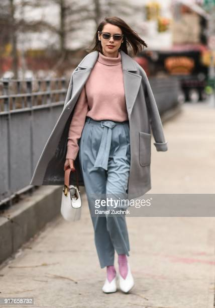 A guest is seen wearing a gray coat pink sweater and baby blue pants outside the Zimmermann show during New York Fashion Week Women's A/W 2018 on...