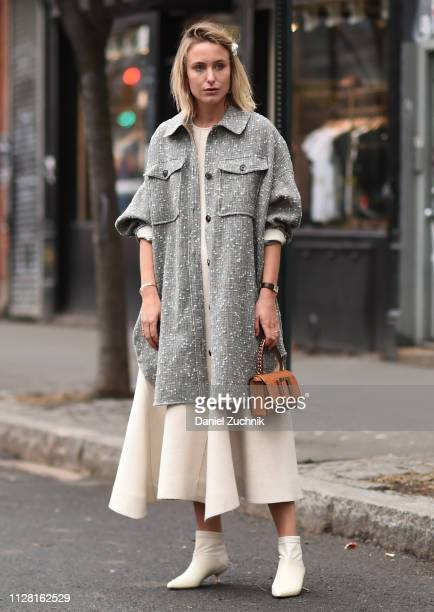 A guest is seen wearing a gray coat white dress brown bag and white booties outside the Collina Strada show during New York Fashion Week Women's...