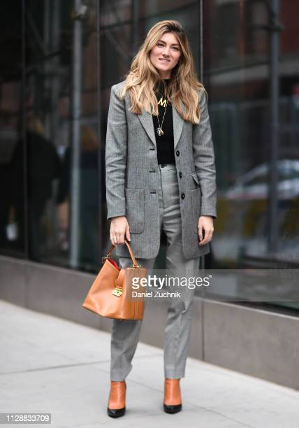 A guest is seen wearing a gray jacket and pants with brown bag and shoes outside the Tibi show during New York Fashion Week Fall/Winter 2019 on...