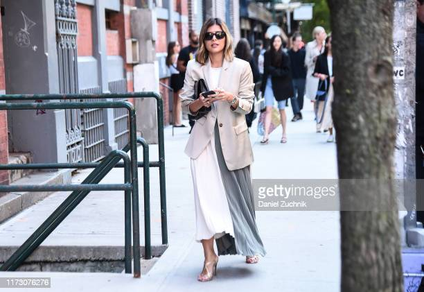 Guest is seen wearing a gray jacket and white and teal skirt outside the Kate Spade show during New York Fashion Week S/S20 on September 07, 2019 in...