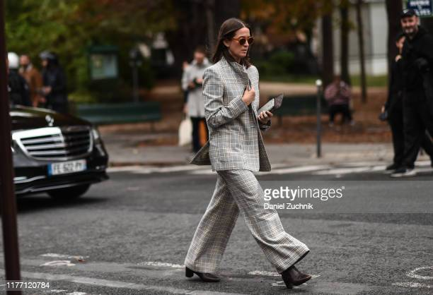 A guest is seen wearing a gray striped suit outside the Maison Margiela show during Paris Fashion Week SS20 on September 25 2019 in Paris France