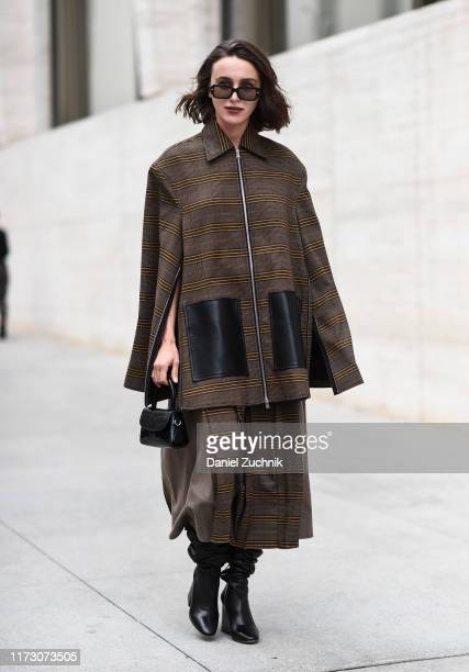 A guest is seen wearing a green and black cape outside the Longchamp show during New York Fashion Week S/S20 on September 07 2019 in New York City