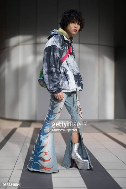 A guest is seen wearing a green crossbody bag black/white design coat colorful denim jeans silver platform shoes during the Amazon Fashion Week TOKYO...