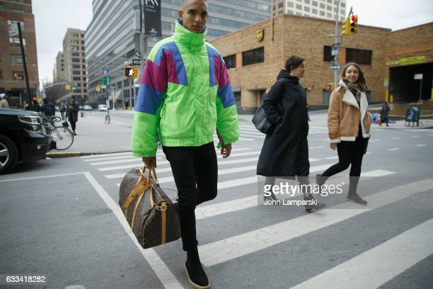 A guest is seen wearing a green ski jacket black pants and a Louis Vuitton bag outisde the Nautica fashion show during New York Men's Fashion Week...