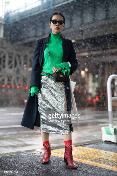 A guest is seen wearing a green sweater silver metallic skirt red shoes and long navy coat during the Amazon Fashion Week TOKYO 2018 A/W on March 21...