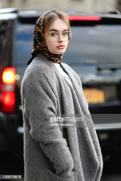 Guest is seen wearing a grey coat and head scarf outside of Spring Studios during New York Fashion Week on February 09, 2020 in New York City.