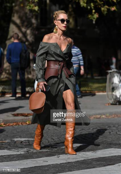 A guest is seen wearing a hunter green dress with brown leather belt and brown boots and bag outside the Sacai show during Paris Fashion Week SS20 on...