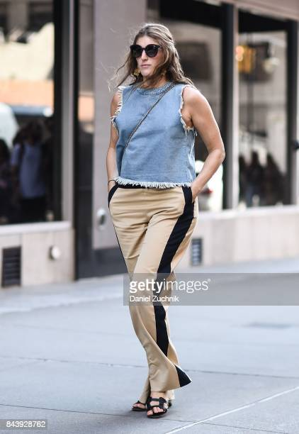 A guest is seen wearing a jean top and brown and black striped pants outside the Tadashi Shoji show during New York Fashion Week Women's S/S 2018 at...