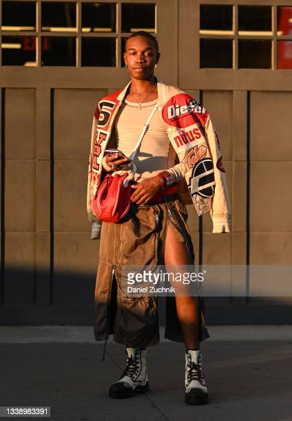 Guest is seen wearing a leather race car inspired jacket and brown pants with a red bag outside the Collina Strada show during New York Fashion Week...