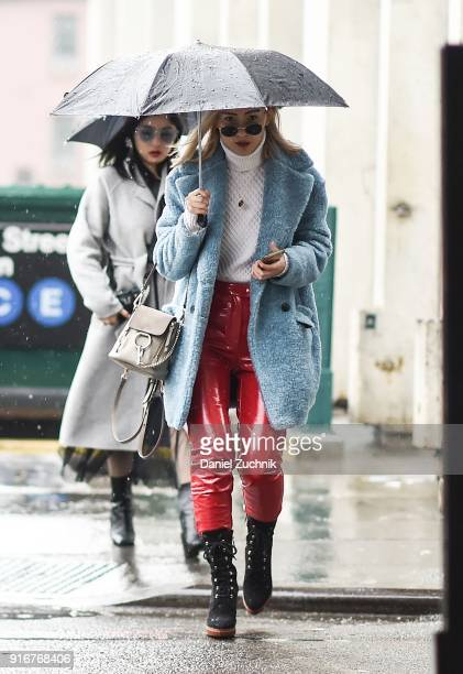 A guest is seen wearing a light blue fur coat and red latex pants outside the Christian Cowan show during New York Fashion Week Women's A/W 2018 on...