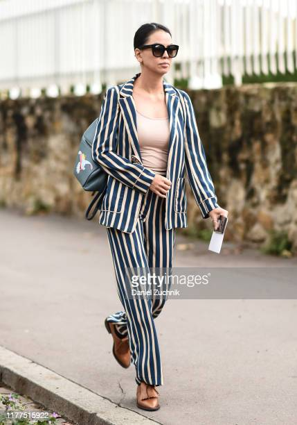 Guest is seen wearing a Loewe striped suit outside the Loewe show during Paris Fashion Week SS20 on September 27, 2019 in Paris, France.
