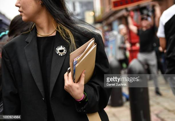 A guest is seen wearing a MK brooch outside the Michael Kors show during New York Fashion Week Women's S/S 2019 on September 12 2018 in New York City