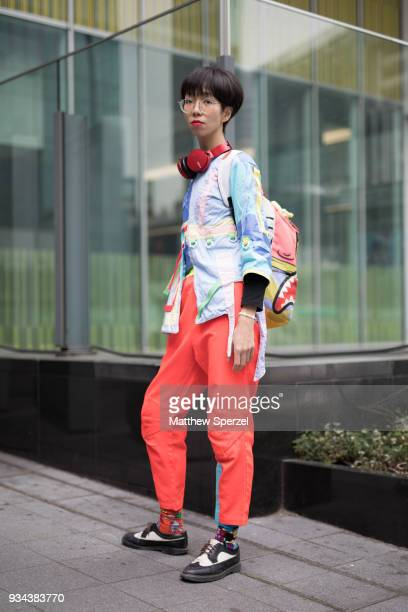 A guest is seen wearing a multicolor pastel shirt red pastel pants black/white leather shoes and Sprayground backpack during the Amazon Fashion Week...
