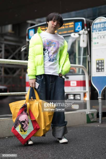 A guest is seen wearing a neon down coat white comic graphic shirt oversized denim pants yellow bag with red scarf during the Amazon Fashion Week...