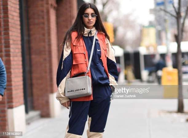 A guest is seen wearing a Nike top and pants with a Marc Jacobs bag outside the Collina Strada show during New York Fashion Week Women's Fall/Winter...
