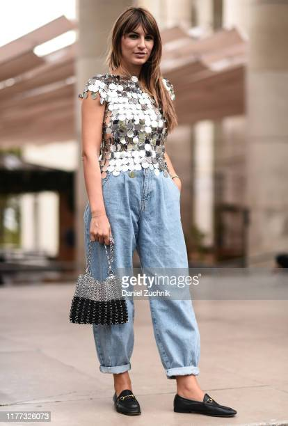 A guest is seen wearing a Paco Rabanne silver top with bag and blue jeans outside the Paco Rabanne show during Paris Fashion Week SS20 on September...