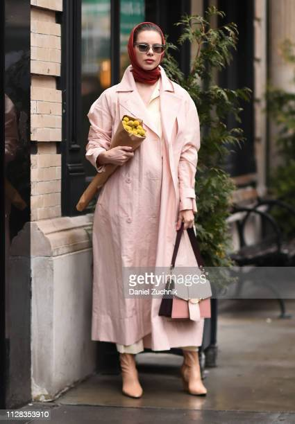 A guest is seen wearing a pink coat and bag with a maroon head scarf outside the Nanushka show during New York Fashion Week Fall/Winter 2019 on...