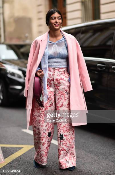 A guest is seen wearing a pink coat light blue sheer top and white and pink floral pants outside the Thom Browne show during Paris Fashion Week SS20...