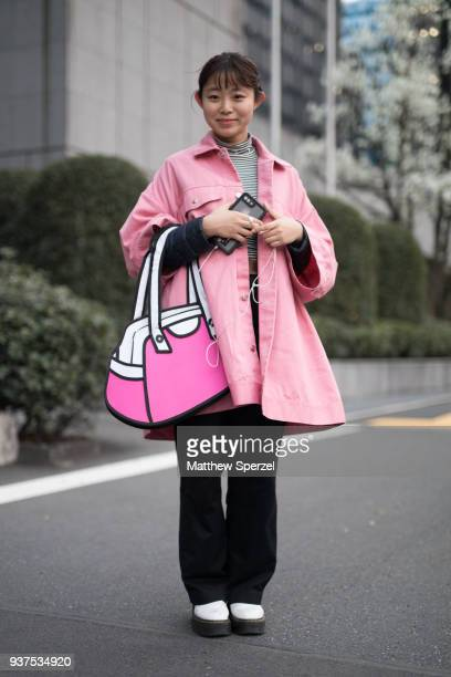 A guest is seen wearing a pink coat striped shirt pink/white cartoon design bag and black pants during the Amazon Fashion Week TOKYO 2018 A/W on...
