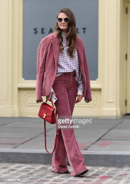 Guest is seen wearing a pink jacket and pants and red bag outside the Tory Burch show during New York Fashion Week: Fall/Winter 2019 on February 10,...