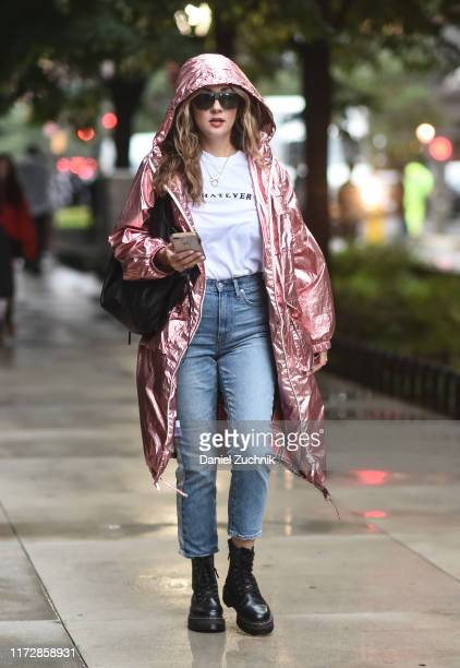 Guest is seen wearing a pink shiny coat, white shirt and blue jeans with black boots outside the Rag & Bone show during New York Fashion Week S/S20...