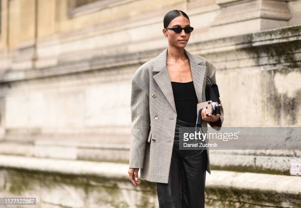 A guest is seen wearing a plaid jacket and black leather pants outside the Unravel show during Paris Fashion Week SS20 on September 25 2019 in Paris...