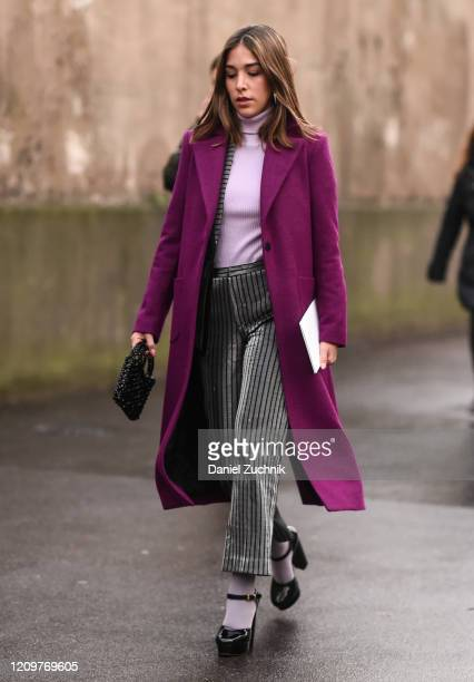 A guest is seen wearing a purple coat purple sweater and gray striped pants outside the Valentino show during Paris Fashion Week AW20 on March 01...