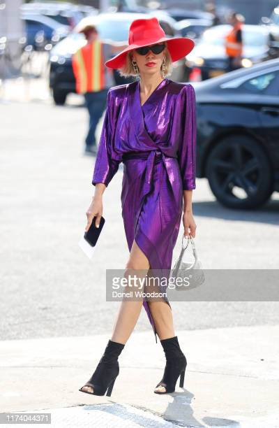 Guest is seen wearing a purple dress with a red hat and black heels during New York Fashion Week on September 11, 2019 in New York City.