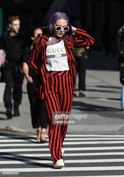 A guest is seen wearing a red and black striped outfit with a Gucci shirt outside the Tadashi Shoji show during New York Fashion Week Women's S/S...
