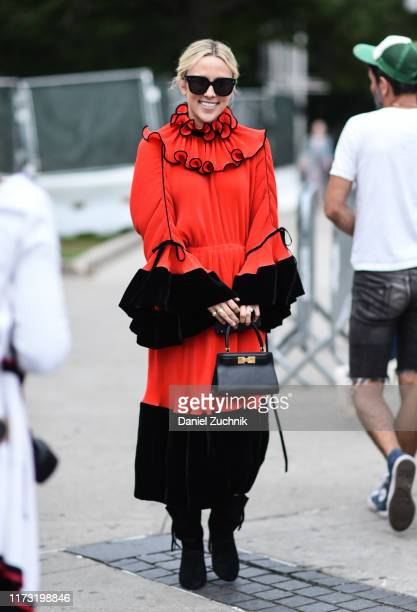 A guest is seen wearing a red and black Tory Burch dress outside the Tory Burch show during New York Fashion Week S/S20 on September 08 2019 in New...
