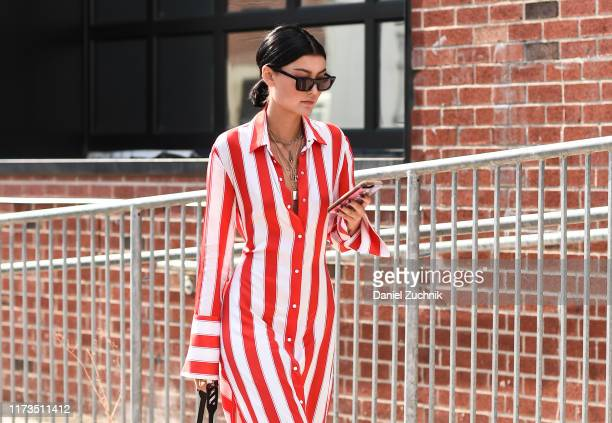 Guest is seen wearing a red and white striped dress and black sunglasses outside the Phillip Lim show during New York Fashion Week S/S20 on September...