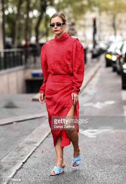 A guest is seen wearing a red dress and light blue heels outside the Redemption show during Paris Fashion Week SS20 on September 26 2019 in Paris...