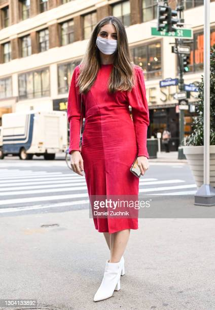 Guest is seen wearing a red dress and white shoes outside the Christian Siriano show during New York Fashion Week F/W21 on February 25, 2021 in New...