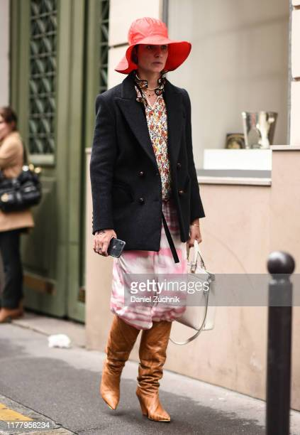 Guest is seen wearing a red hat, black jacket, floral top, tie dye pants and brown leather boots outside the Thom Browne show during Paris Fashion...