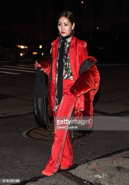 A guest is seen wearing a red puff coat red velvet suit and floral top outside the Marc Jacobs show during New York Fashion Week Women's A/W 2018 on...