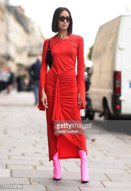 Guest is seen wearing a red Unravel dress and pink boots outside the Unravel show during Paris Fashion Week SS20 on September 25, 2019 in Paris,...