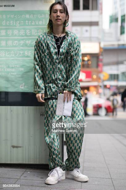A guest is seen wearing a satin green outfit with white sneakers during the Amazon Fashion Week TOKYO 2018 A/W on March 19 2018 in Tokyo Japan