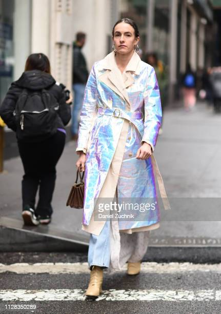 A guest is seen wearing a shiny overcoat with an offwhite coat underneath outside the Kate Spade show during New York Fashion Week Fall/Winter 2019...