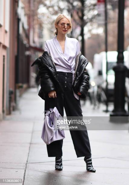 Guest is seen wearing a silk purple top and a black vegan leather Nanushka coat outside the Nanushka show during New York Fashion Week: Fall/Winter...