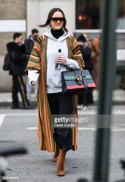 A guest is seen wearing a striped coat with gray hoodie and brown shoes outside of the Rochambeau show during New York Fashion Week Men's AW17 on...