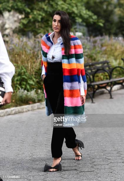 Guest is seen wearing a striped fur coat, white top, black pants and black lace heels outside the Carolina Herrera show during New York Fashion Week...