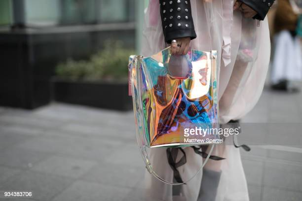 A guest is seen wearing a studded black leather jacket with PVC bag and pink schear pants with black boots during the Amazon Fashion Week TOKYO 2018...