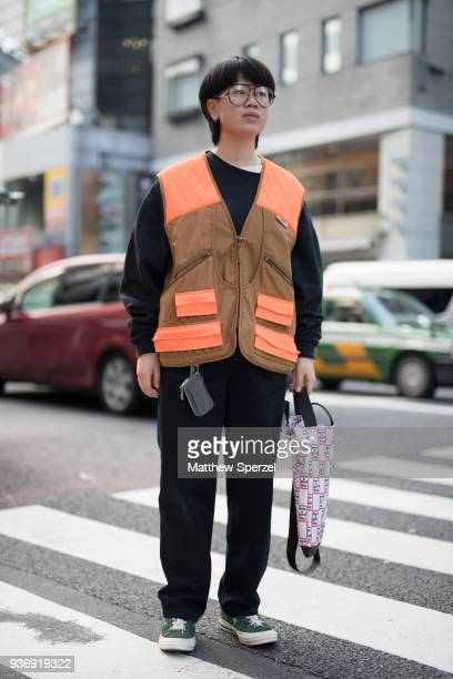 A guest is seen wearing a tan/orange vest with black outfit during the Amazon Fashion Week TOKYO 2018 A/W on March 22 2018 in Tokyo Japan