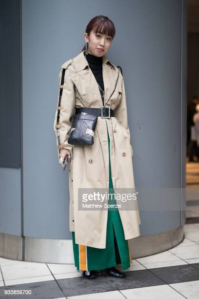 A guest is seen wearing a taupe trench coat black sweater and green/yellow skirt with black leather belt and hip bag during the Amazon Fashion Week...