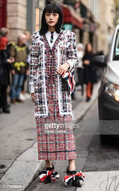Guest is seen wearing a Thom Browne jacket and dress and lace Thom Browne shoes with bag outside the Thom Browne show during Paris Fashion Week SS20...