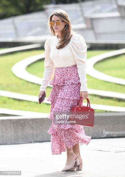 Guest is seen wearing a Tory Burch blouse and floral skirt with a red leather bag outside the Tory Burch show during New York Fashion Week S/S20 on...