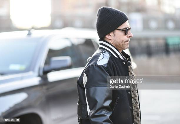 A guest is seen wearing a varsity jacket and black beanie outside the Esteban Cortazar show during New York Fashion Week Women's A/W 2018 on February...