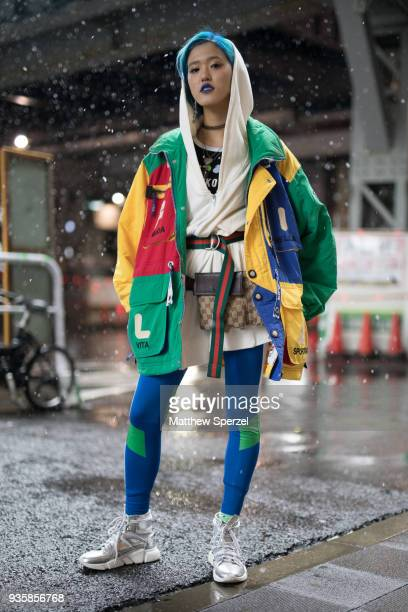 A guest is seen wearing a vintage green/yellow/red/blue jacket with cream hoodie blue/green spandex silver sneakers Gucci belt and Louis Vuitton hip...