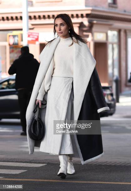 A guest is seen wearing a white and black leather fur coat white top and skirt outside the Tory Burch show during New York Fashion Week Fall/Winter...