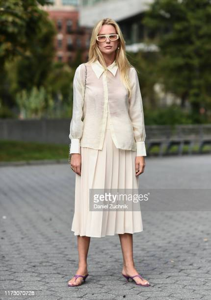 Guest is seen wearing a white blouse, white skirt and white sunglasses outside the Area show during New York Fashion Week S/S20 on September 07, 2019...